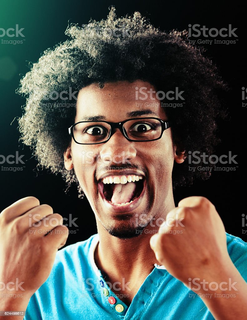 Triumphant young man with afro and spectacles cheers, fists clenched stock photo