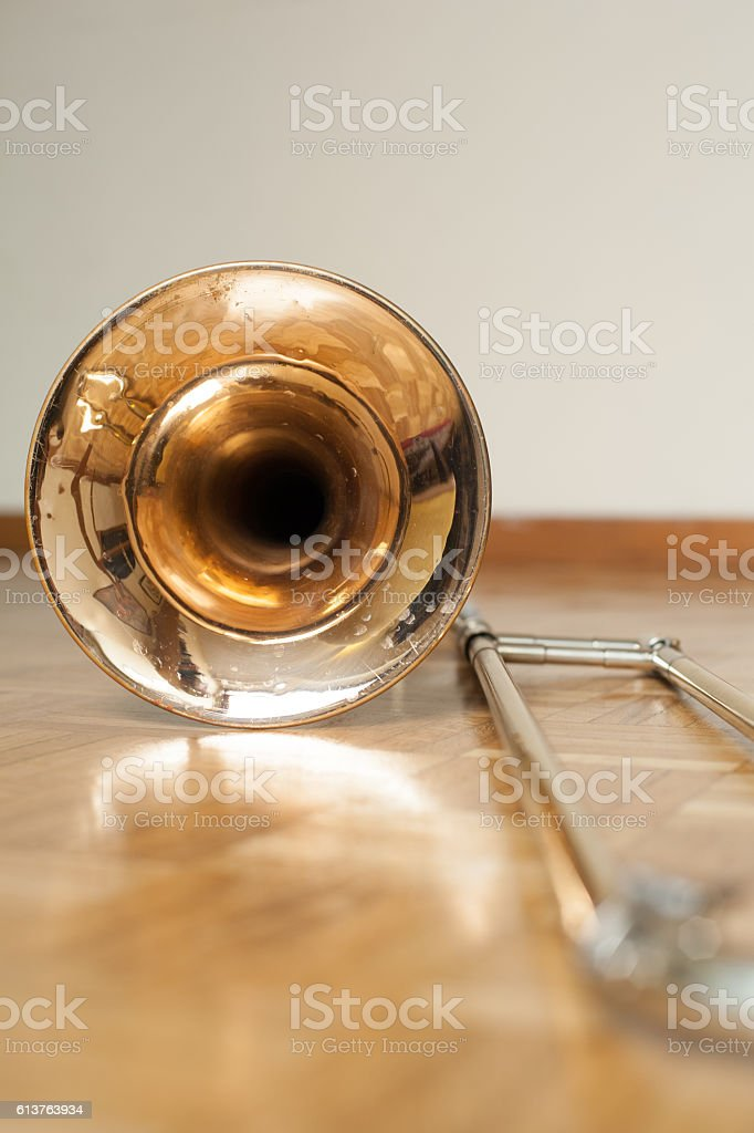 Trombone on wooden floor detail stock photo
