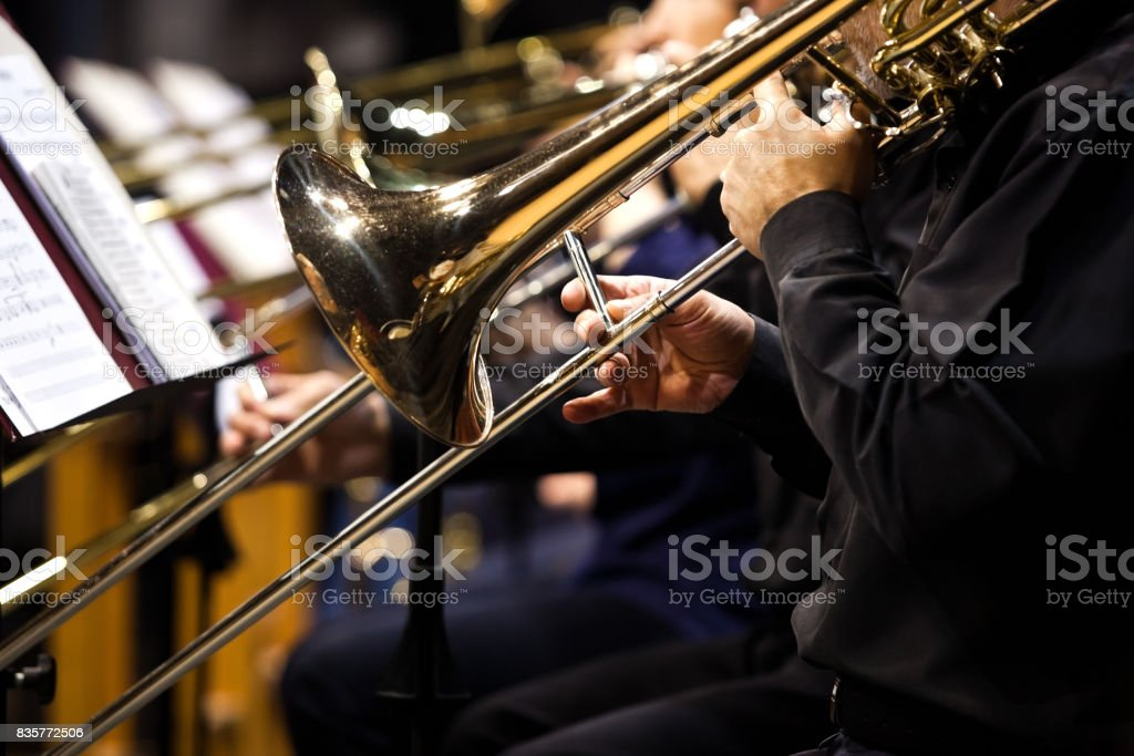 Trombones in the hands of musicians in the orchestra stock photo