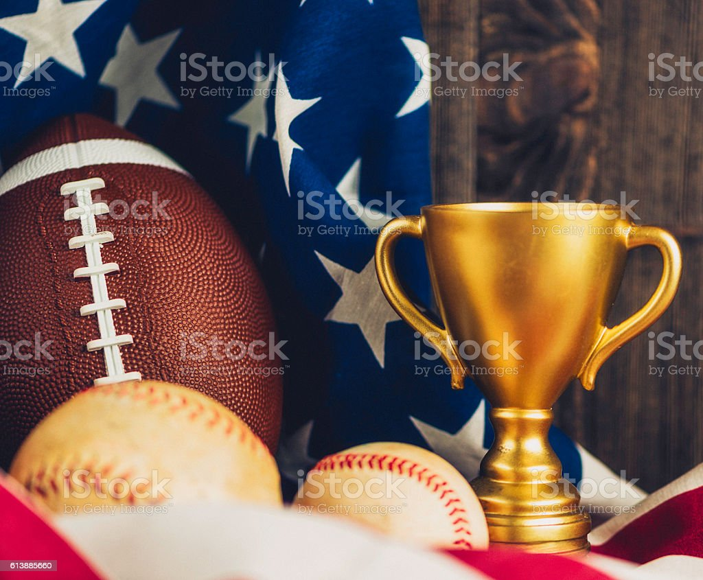 Trophy, football, softball and baseball in front of American flag