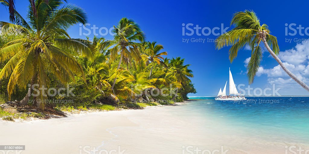 Tropical beach and sailing boat stock photo