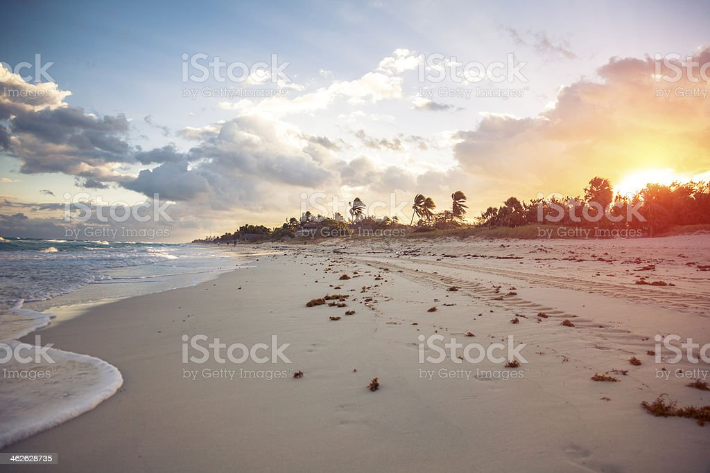 Tropical beach at sunset with gentle waves stock photo