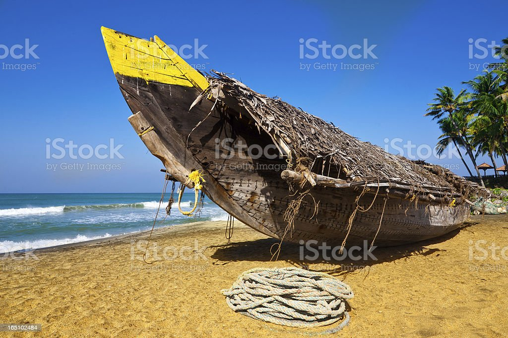 Tropical beach landscape with fishing boat at ocean coast royalty-free stock photo