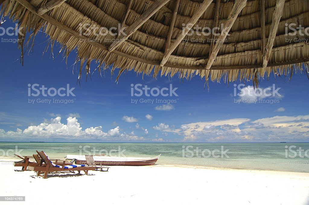 Tropical beach resort with bamboo hut in the foreground royalty-free stock photo