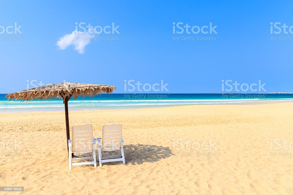 Tropical beach scenery with parasol and deck chairs in Boavista stock photo