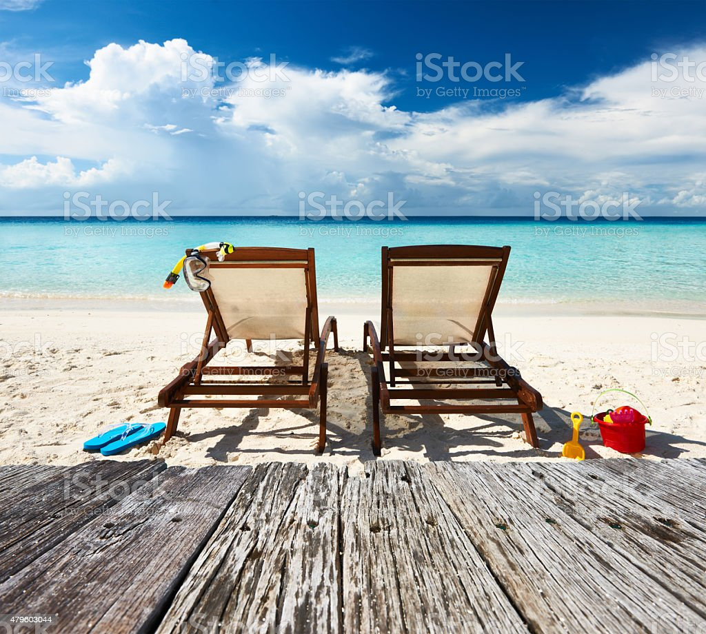 Tropical beach with chaise lounge stock photo