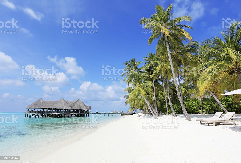 Tropical beach with deck chairs and bungalows on the water stock photo