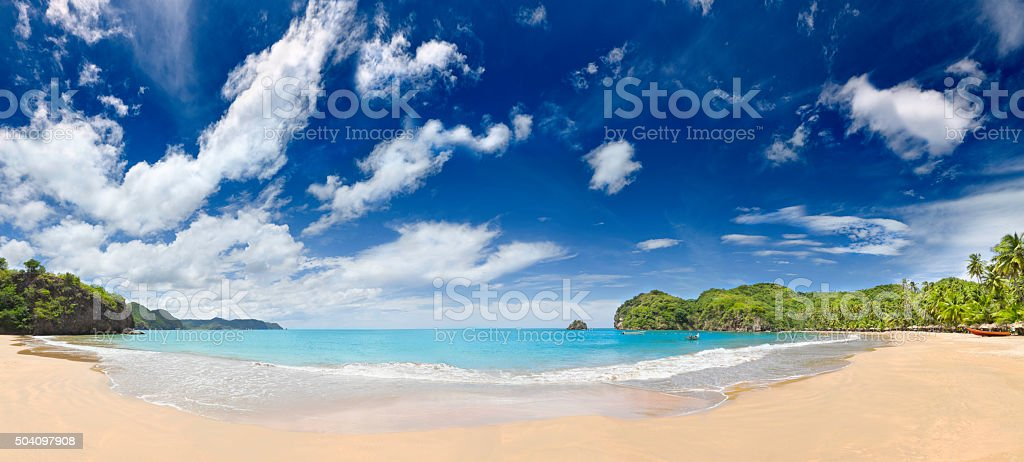 Tropical beach with huts, coconut trees and, deep blue sky stock photo