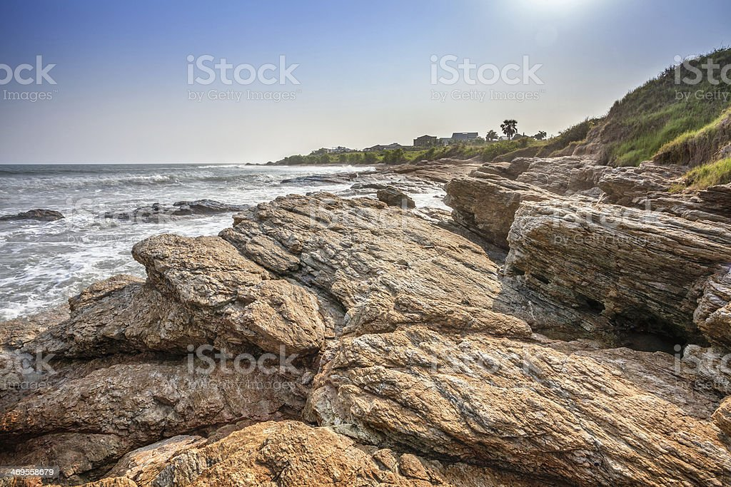 Tropical beach with waves crashing on rocks in West Africa stock photo