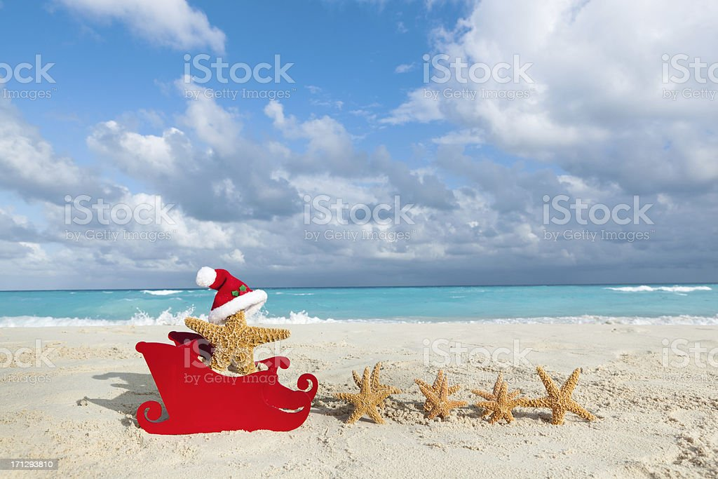 Tropical Christmas Beach Vacation Santa Claus with Starfish and Sleigh stock photo
