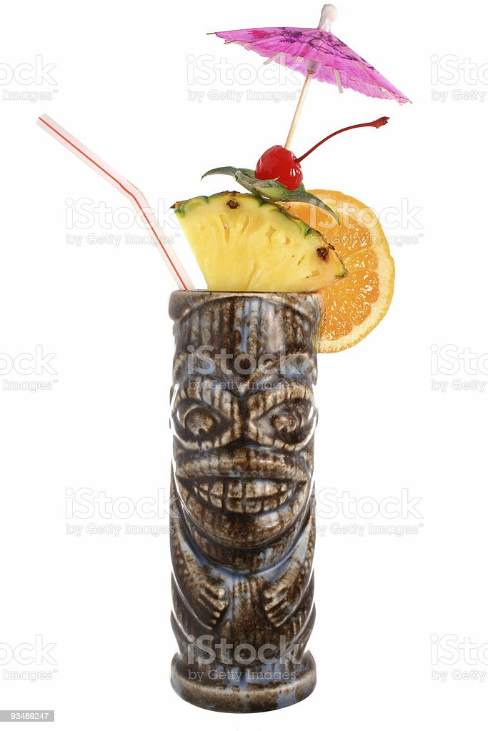 A tropical cocktail in a cup resembling a carved statue stock photo