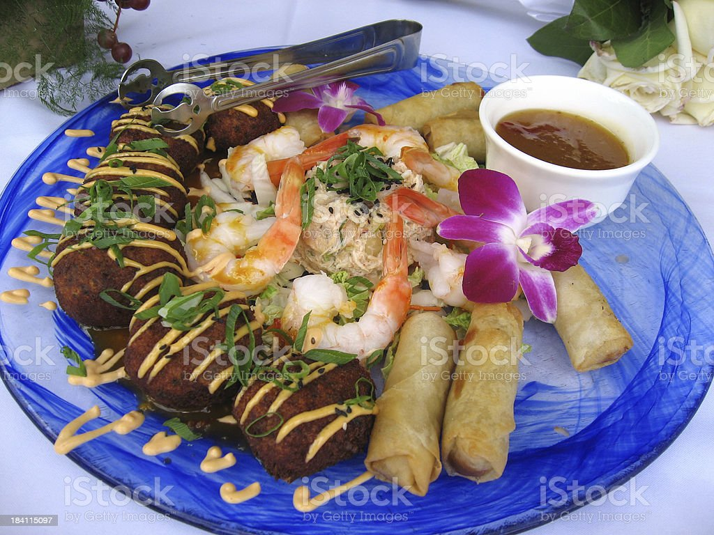 Tropical feast with shrimp, crab cakes and spring rolls stock photo
