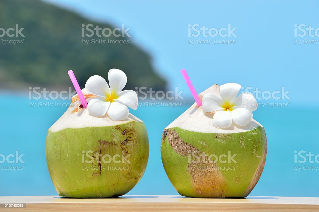 Tropical fresh coconut cocktail decorated plumeria on tropical c stock photo