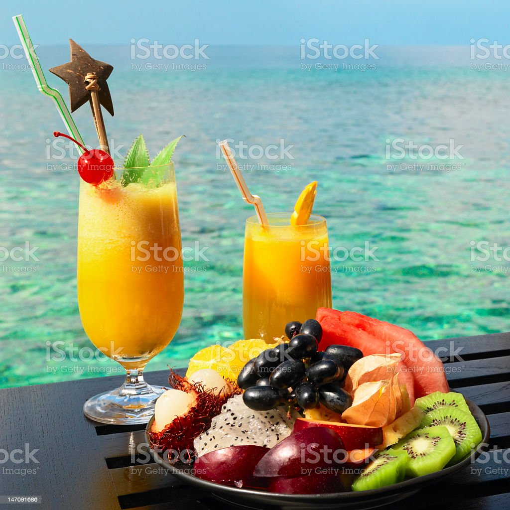 Tropical fruit platter and drinks in front of blue ocean royalty-free stock photo