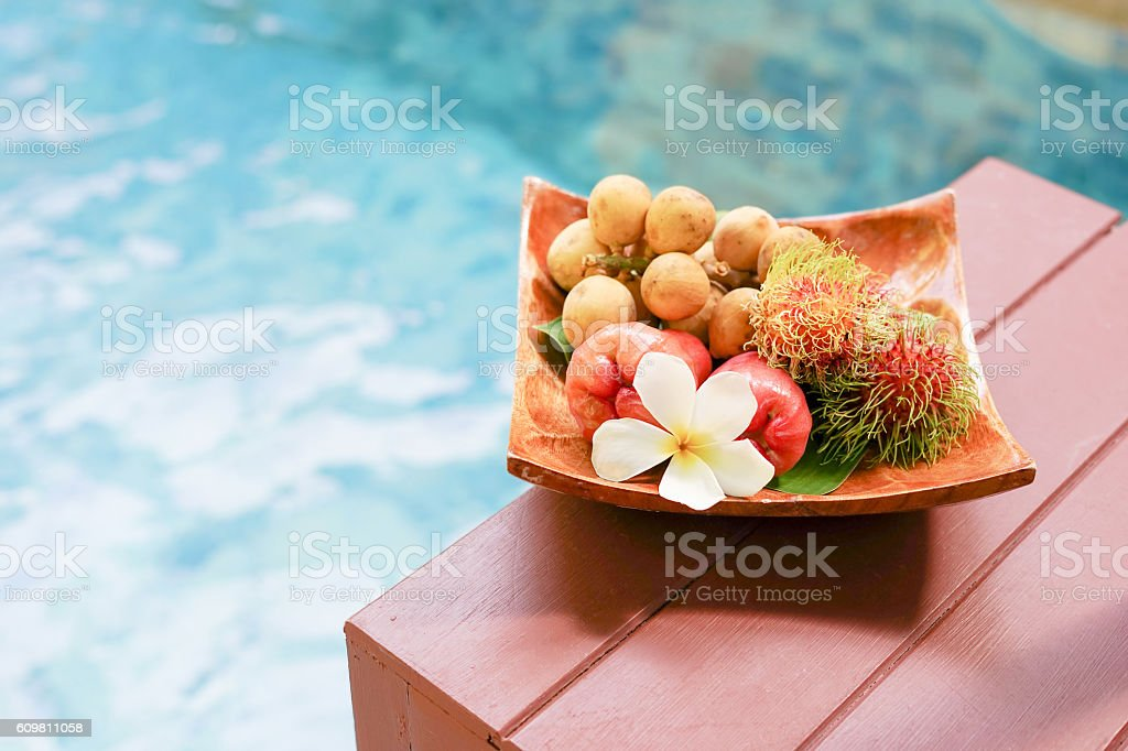 tropical fruits and plmeria on wooden tray stock photo