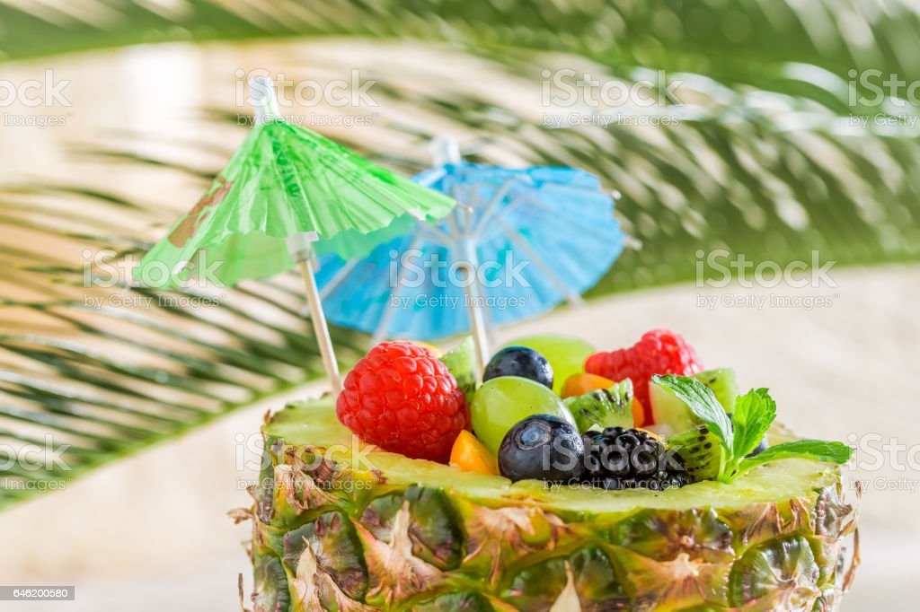 Tropical fruits salad in pineapple on sandy beach stock photo