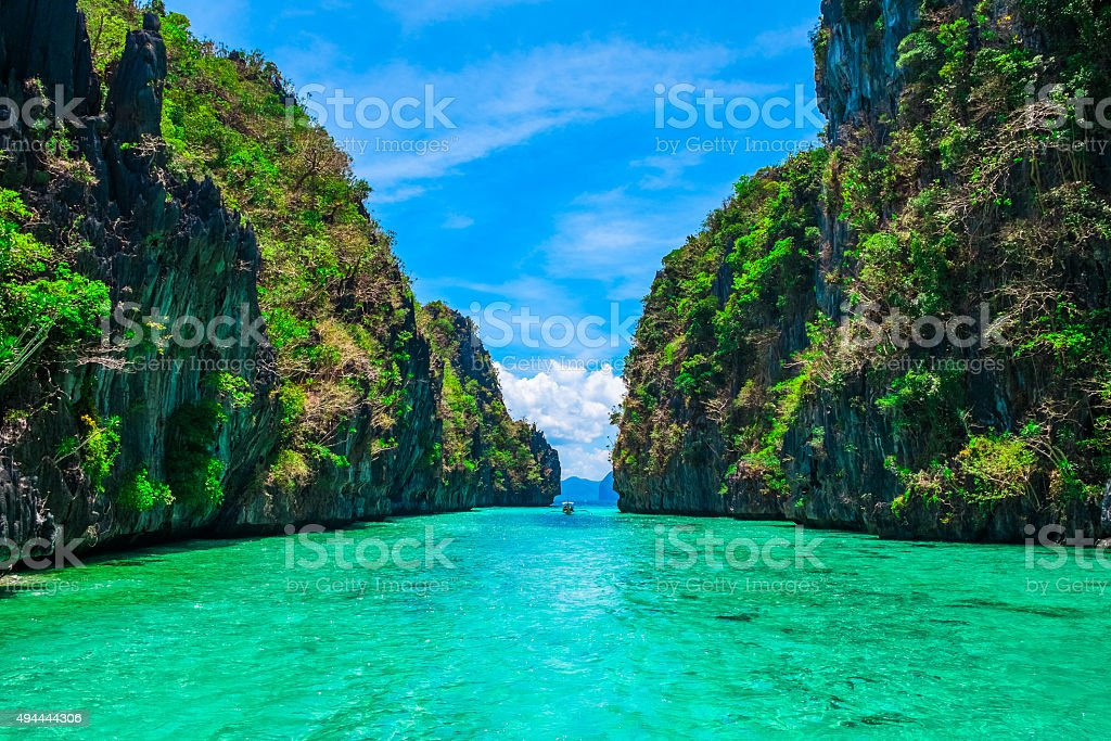 Tropical landscape with rock islands, lonely boat and crystal clear...