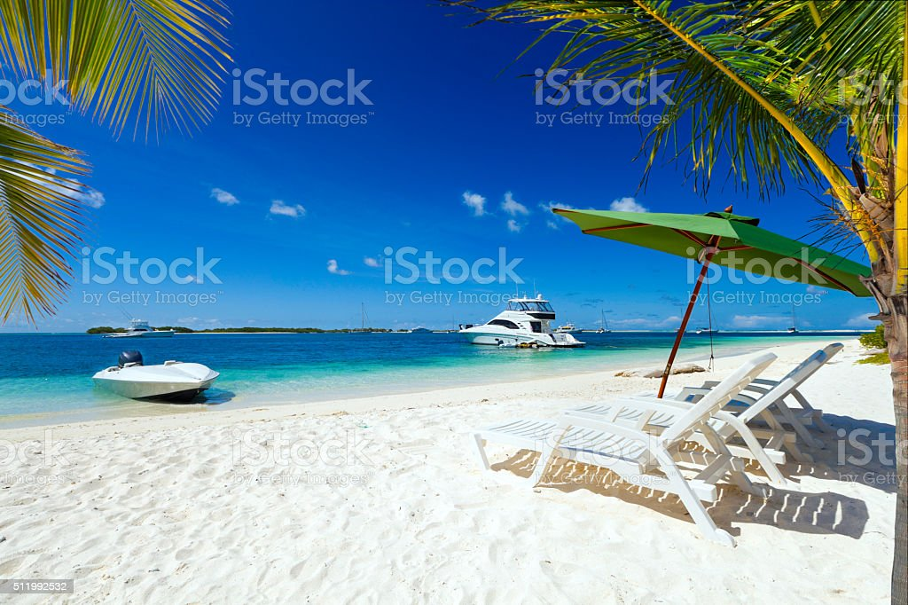 Tropical paradise beach with coconut trees and yachts stock photo