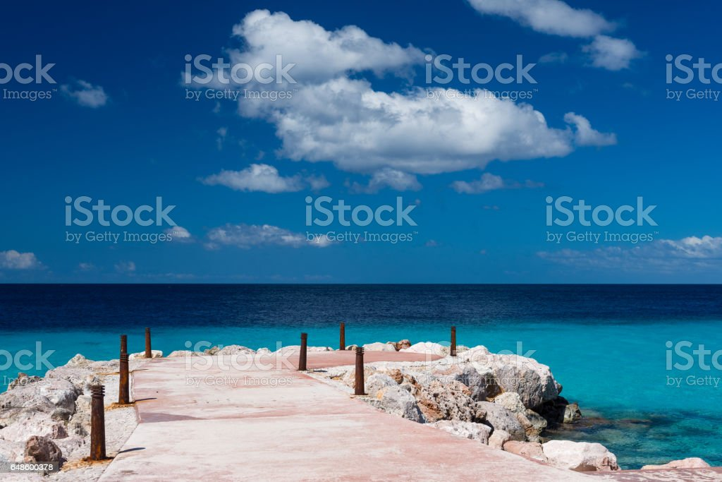 Tropical paradise - pier and blue ocean, sunny day and blue sky, nobody stock photo