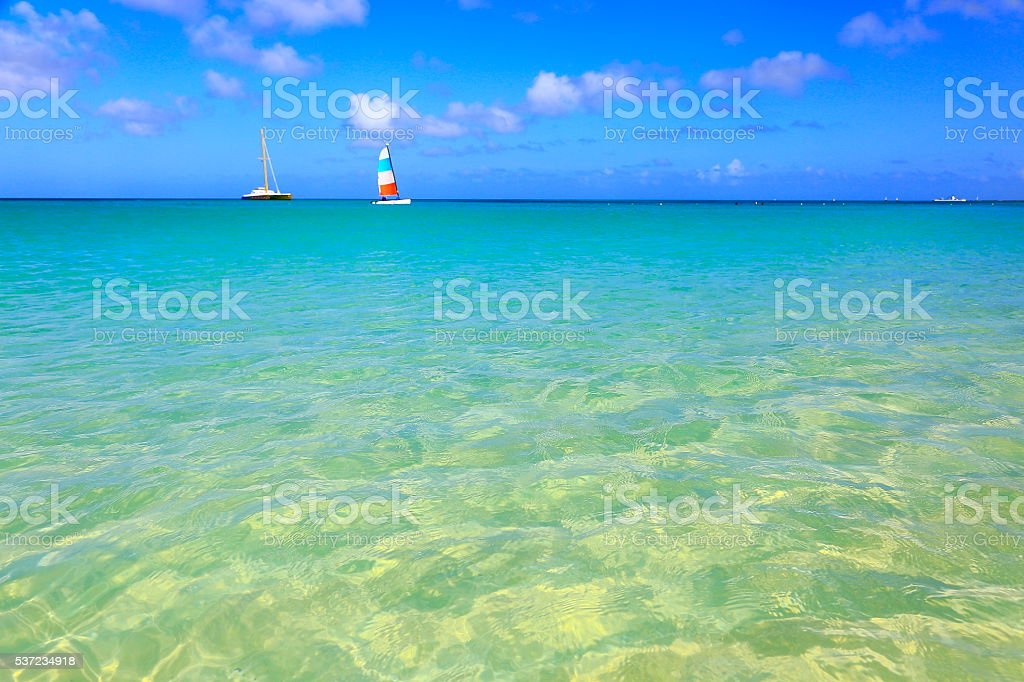 Tropical paradise relax: turquoise caribbean beach, yachts sailing, Aruba, Antilles stock photo
