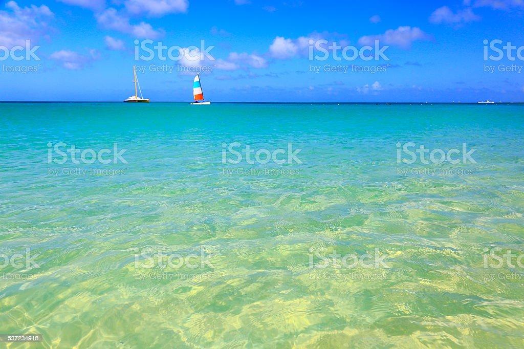 Tropical paradise relax: turquoise caribbean beach, yachts sailing, Aruba, Antilles stock photo