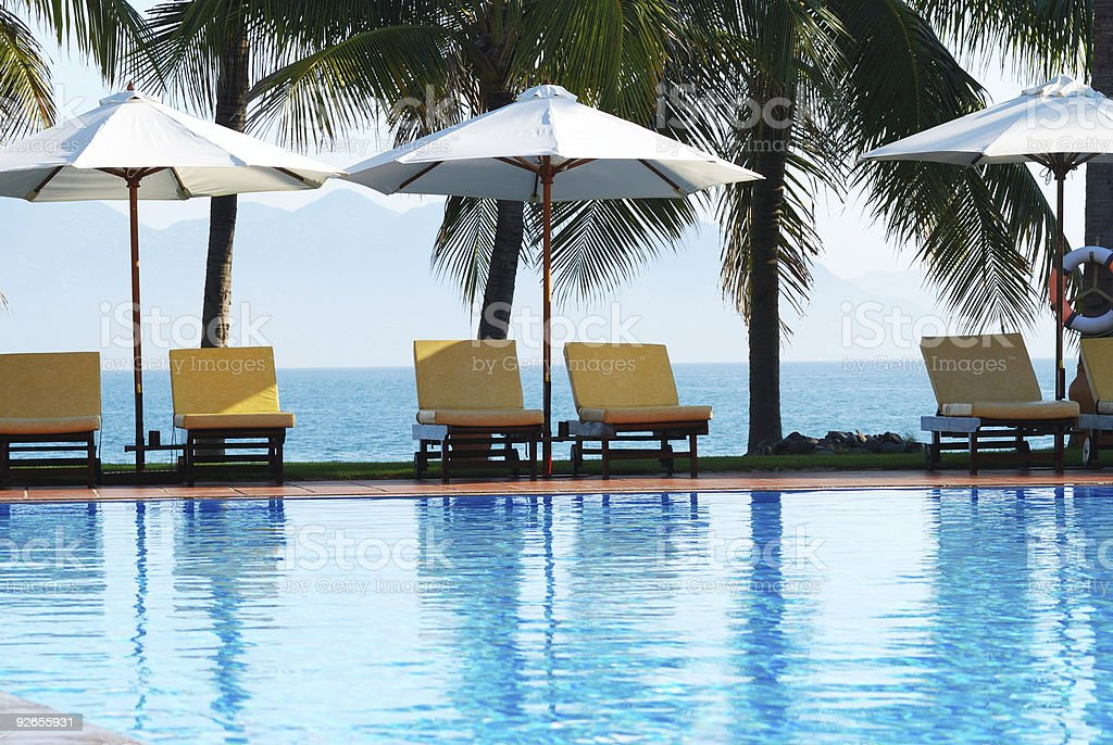 Tropical pool with sitting area and umbrellas  royalty-free stock photo