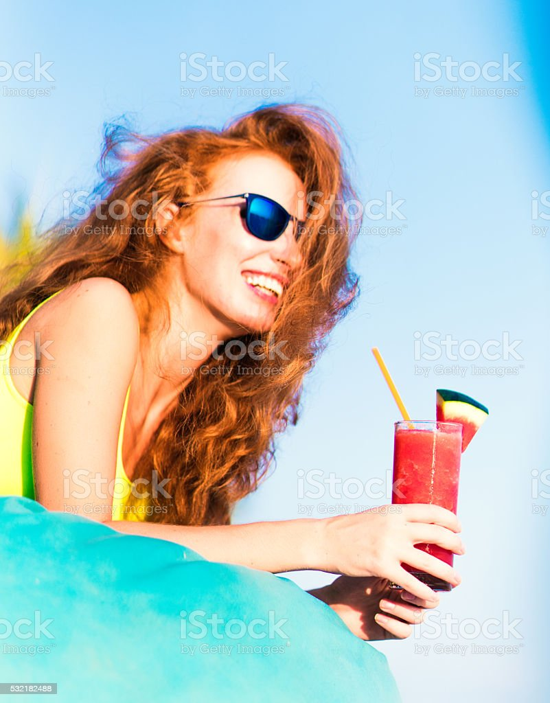 Tropical red cocktail in hand of a young woman stock photo