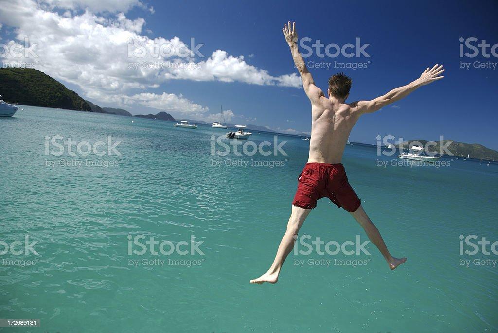 Tropical Spreadeagle Getaway Jump Red Shorts royalty-free stock photo
