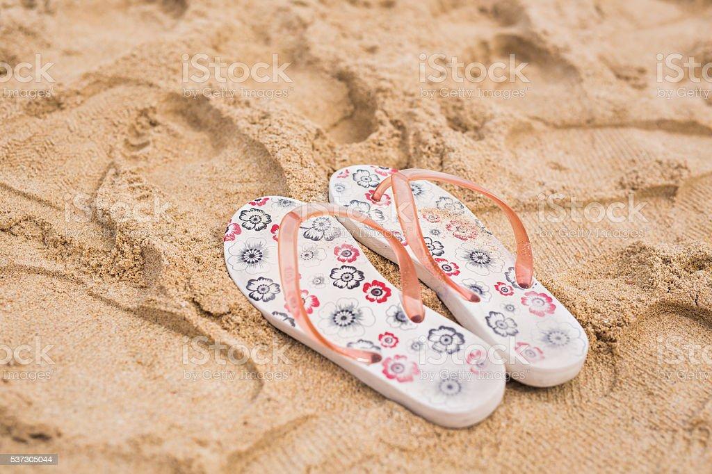 Tropical vacation concept - Flipflops on a sandy ocean beach stock photo