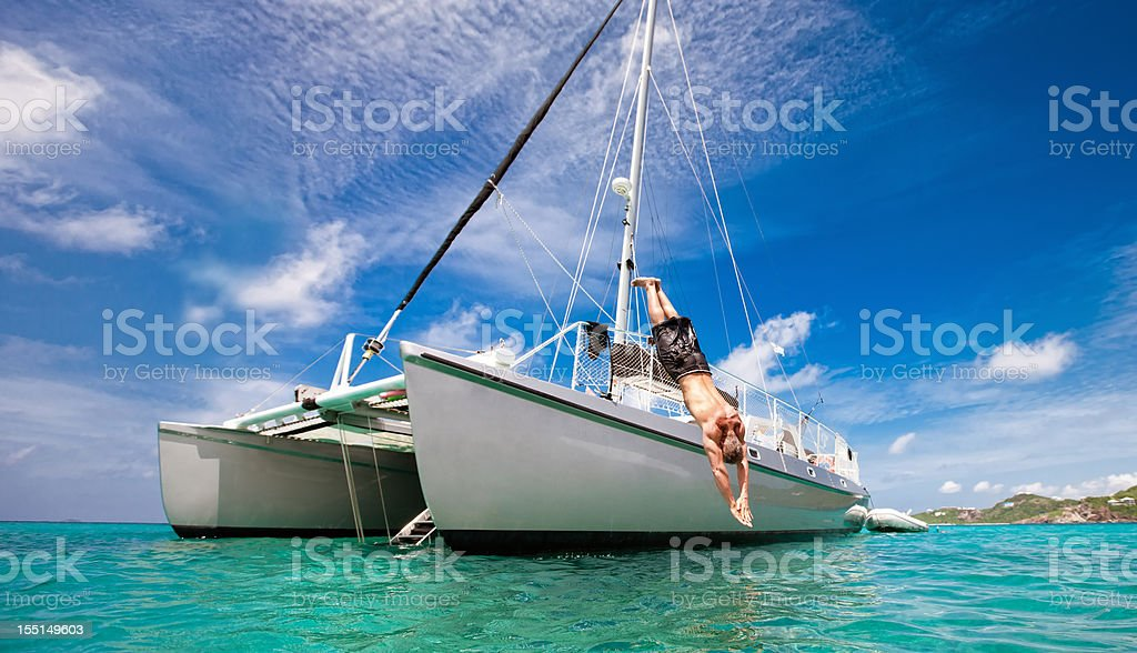 Tropical Vacation: Man Diving Off Sailboat stock photo