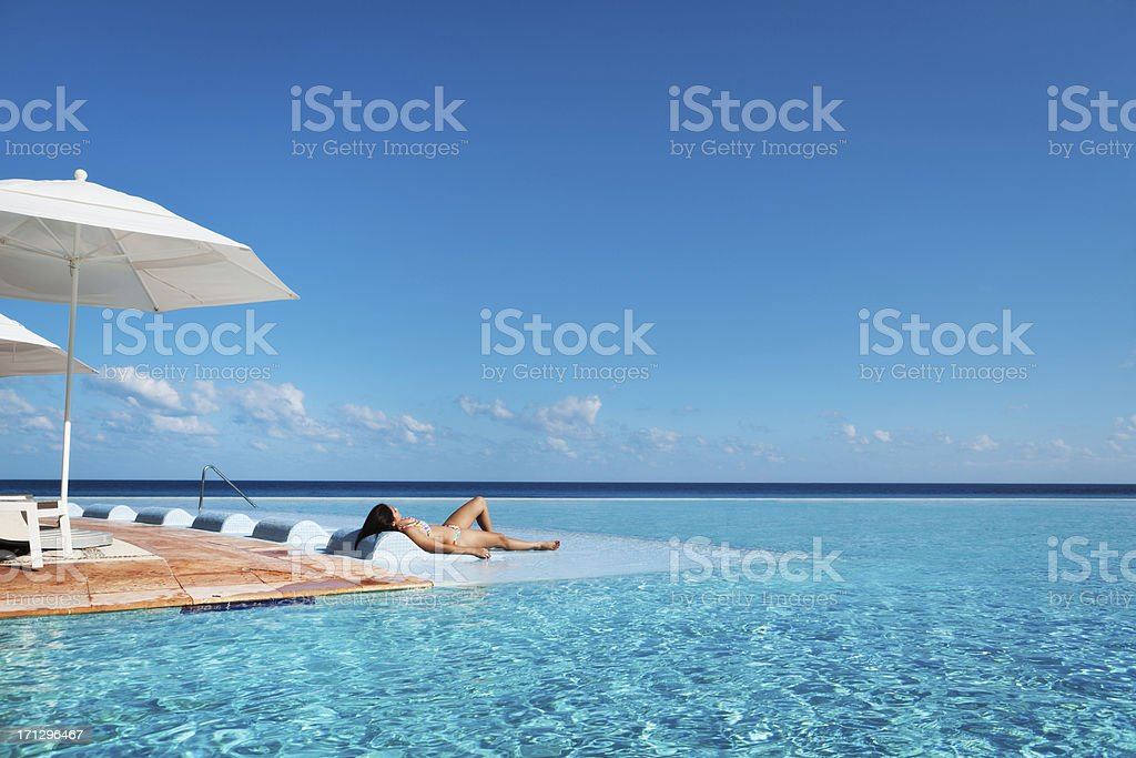 Tropical Vacation Resort Hotel Relaxing in Infinity Pool Hz royalty-free stock photo