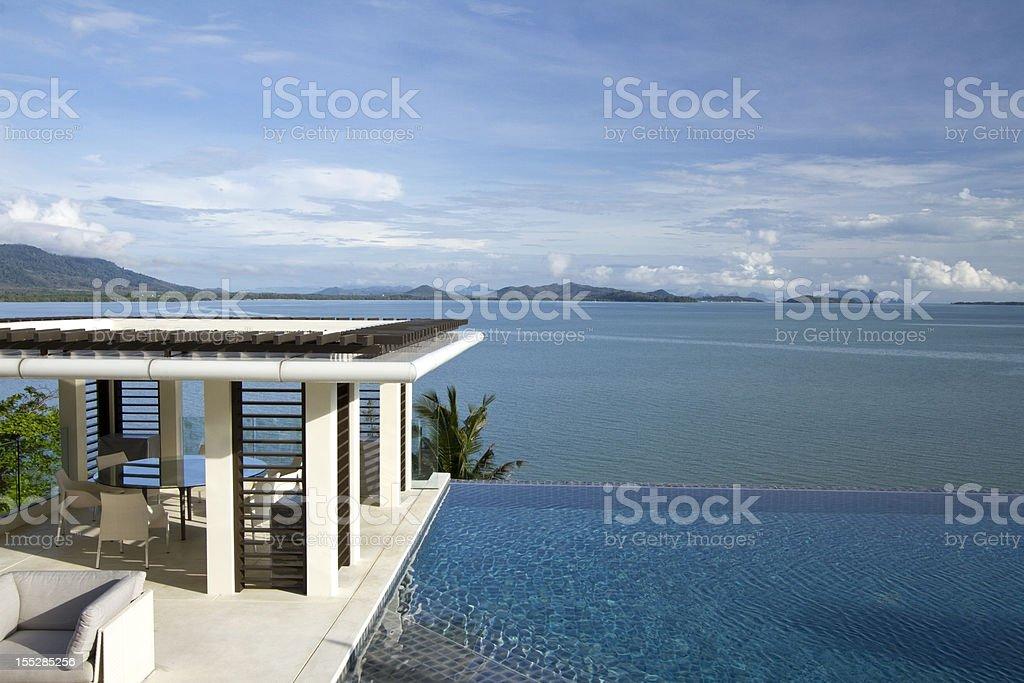 Tropical villa swimming pool facing the sea royalty-free stock photo