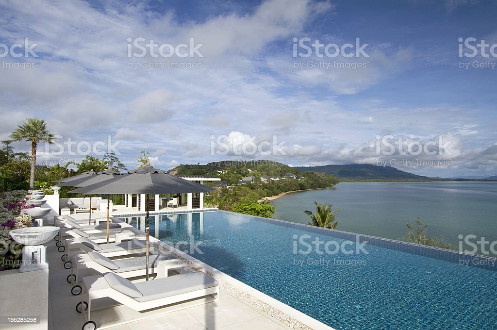 Tropical villa with a row of armschairs facing the sea royalty-free stock photo