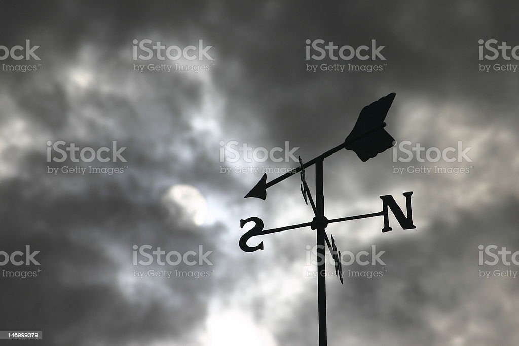 Trouble ahead! Weathervane and storm clouds stock photo