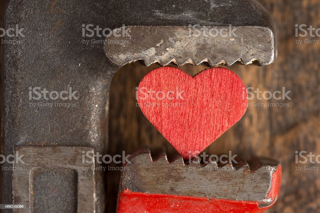 Troubled Love: Red Heart Squeezed by Wrench stock photo
