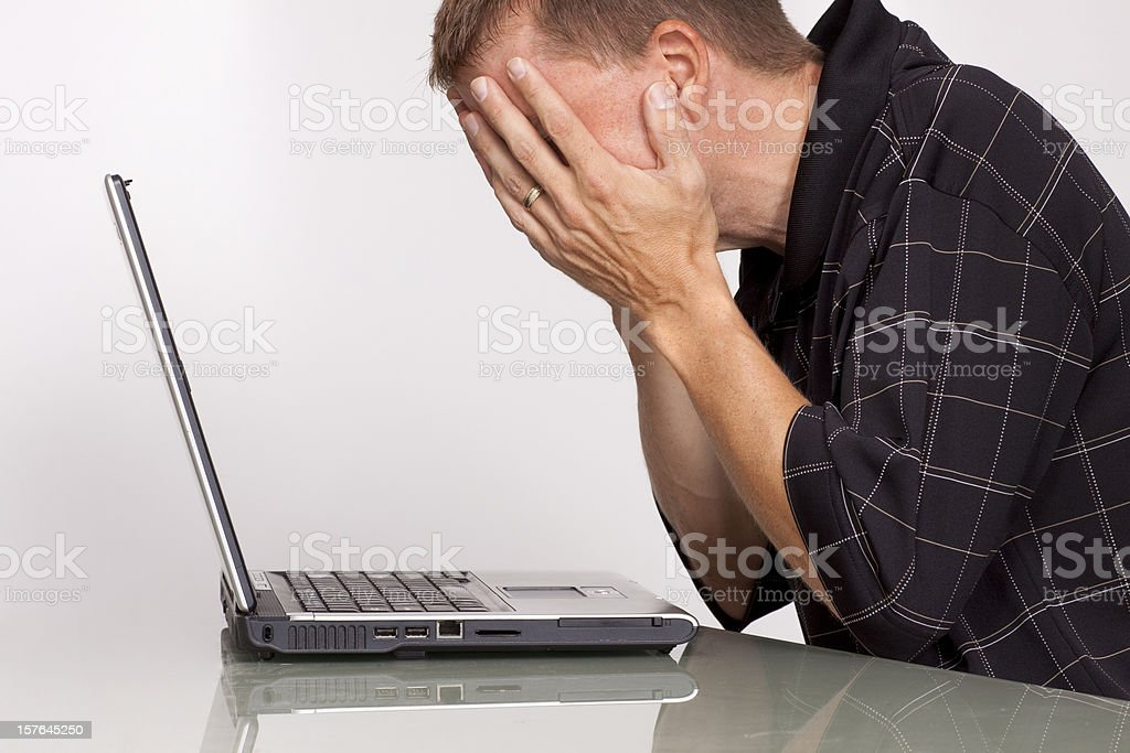Troubled man with laptop computer stock photo