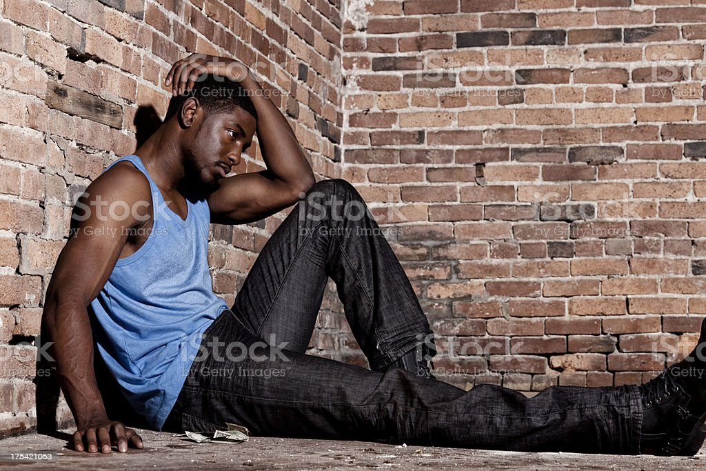 Troubled man with sad face sitting by the brick wall stock photo