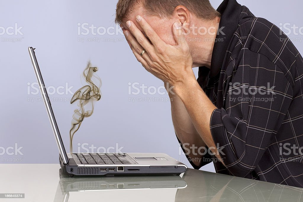 Troubled man with smoking laptop computer stock photo