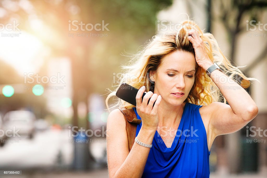 Troubled mature woman listening to bad news on speaker phone stock photo