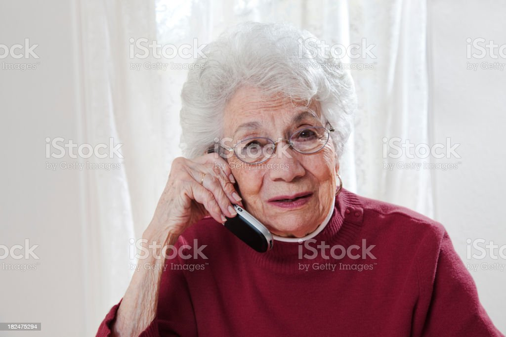 troubled senior woman talking on phone stock photo