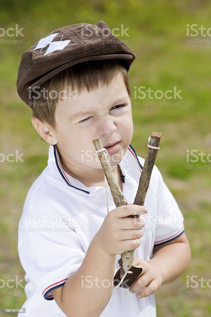 Troublemaker. Boy with slingshot stock photo