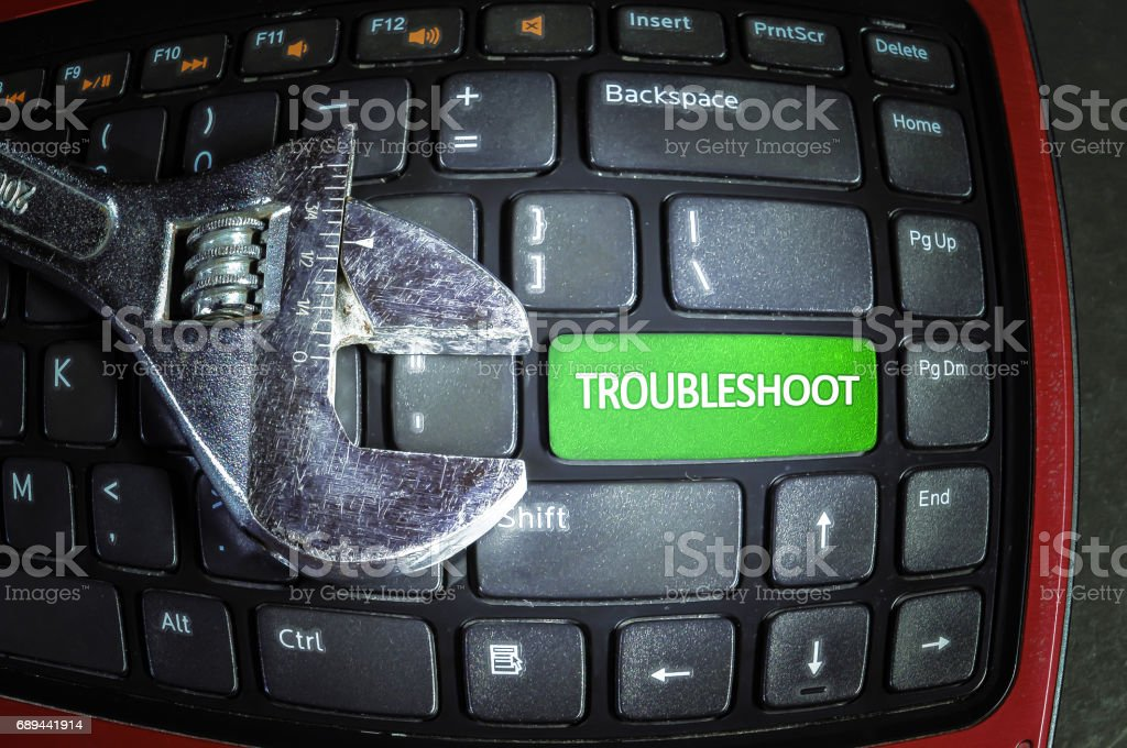 Troubleshoot button on dirty laptop keyboard with wrench tool. Fish eye effect. stock photo