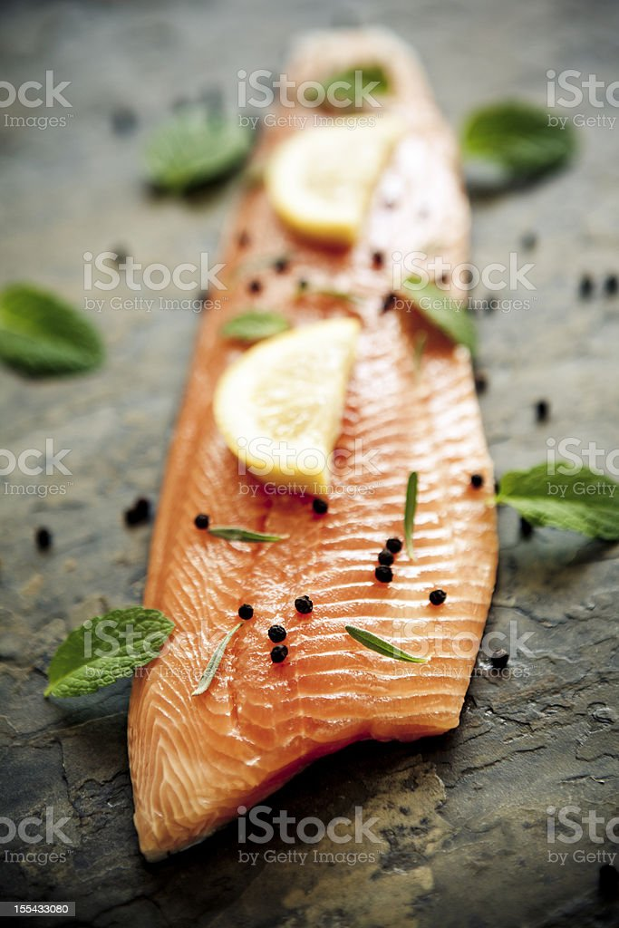 Trout fillet with lemon and capers on a stone surface stock photo