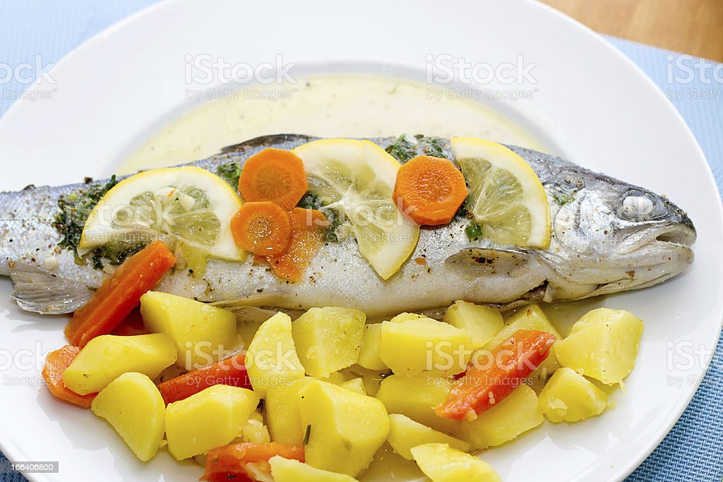 Trout fish with lemon slices and boiled potatoes stock photo