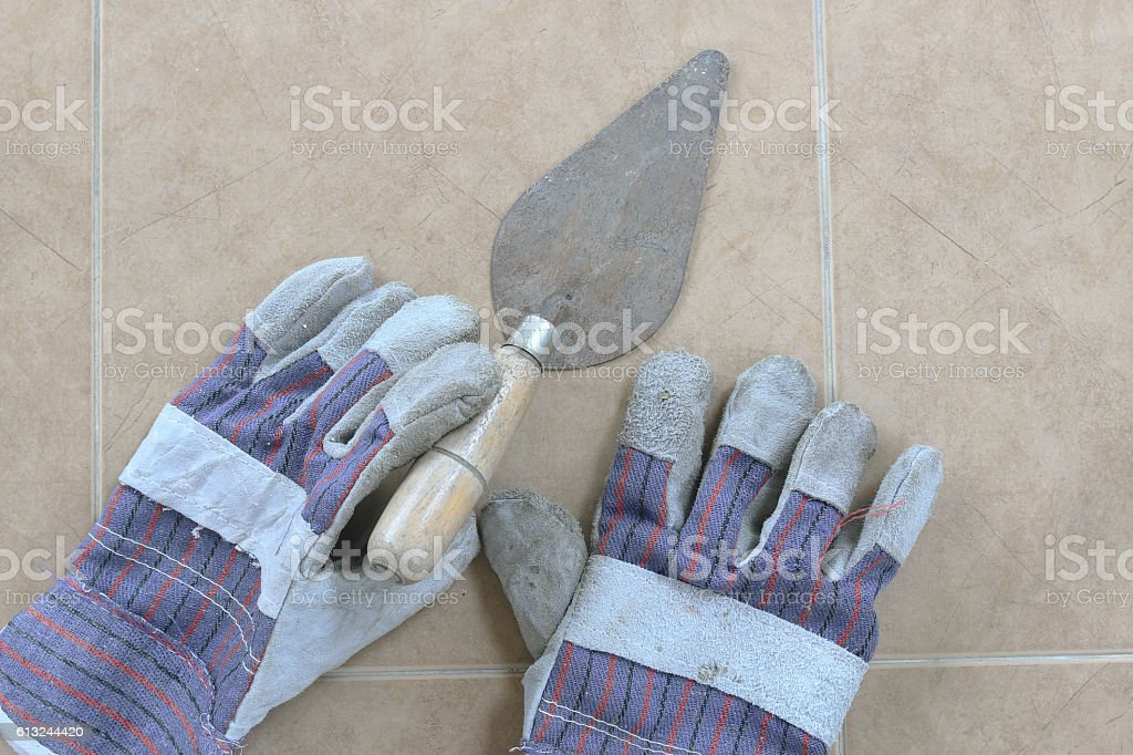 Trowel and construction gloves stock photo