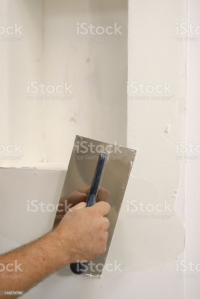 A trowel smoothing white parget on the wall royalty-free stock photo