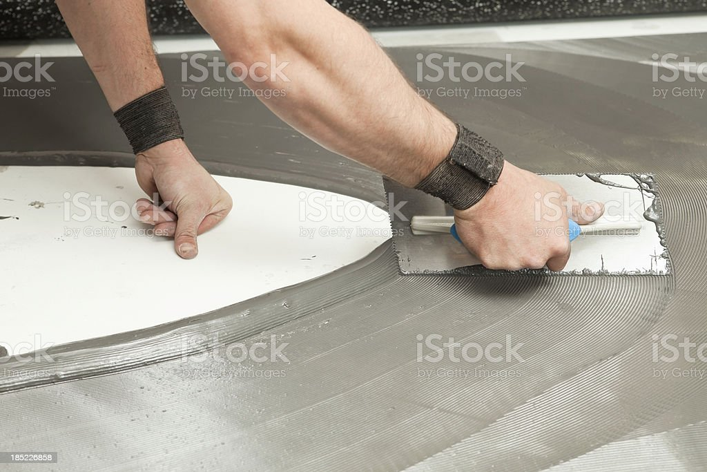 Troweling Adhesive for Recycled Rubber Floor stock photo