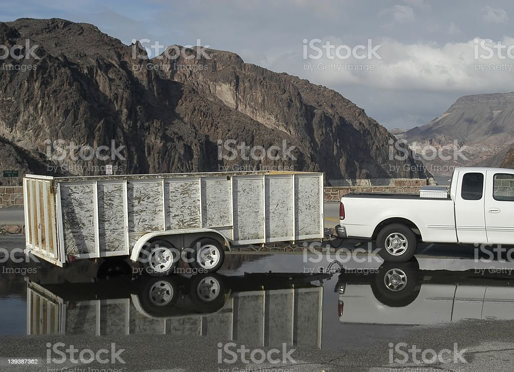 Truck and trailer parked in a large puddle in the foothills stock photo