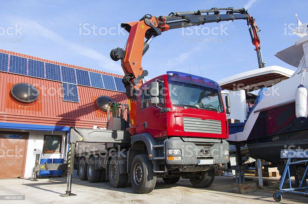 Truck crane lifting a yacht stock photo