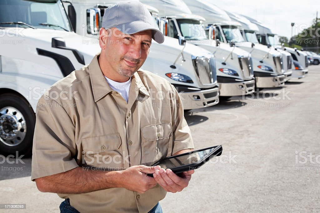 Truck driver in front of big rigs with digital tablet royalty-free stock photo